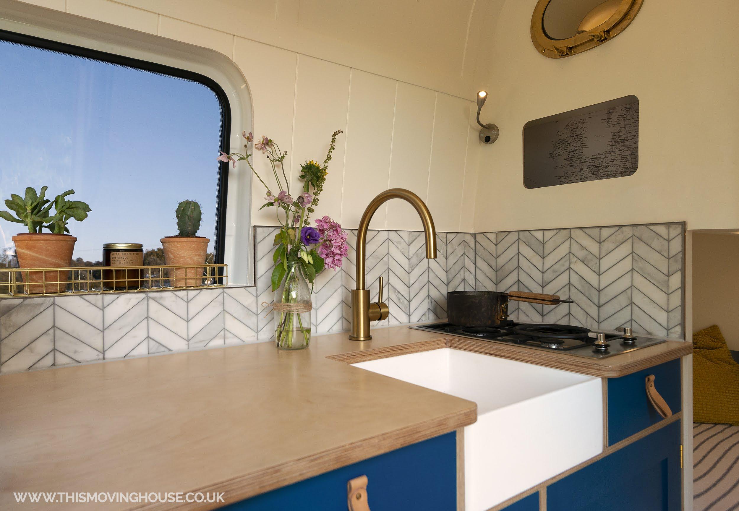 camper van kitchen with belfast sink and copper edge on backsplash
