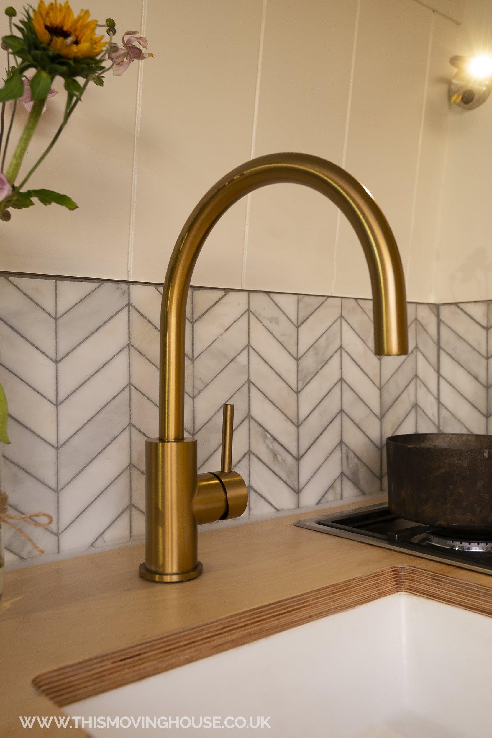 Gold tap in a camper van kitchen